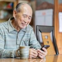 Un homme âgé manipule son téléphone cellulaire en souriant.