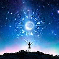 Des signes astrologiques figurent dans le ciel nocturne et une femme les regarde, les bras dans les airs.