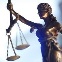 Une statue de femme brandissant une balance, symbole de la justice.