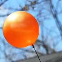 Un ballon de plastique orange flotte dans les airs.