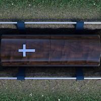 Un cercueil est déposé en terre, prêt à être enseveli.