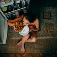 Une femme mange une pointe de pizza pendant la nuit.
