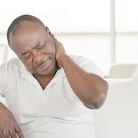 Un homme dépose sa main gauche derrière son cou, où il éprouve visiblement de la douleur.