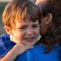 Un enfant pleure dans les bras de sa mère.