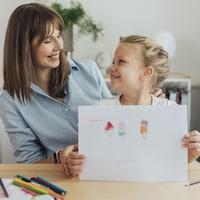 Une petite fille montre avec fierté un dessin à sa mère souriante.