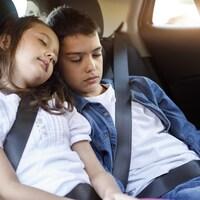 Deux enfants dorment d'une voiture.