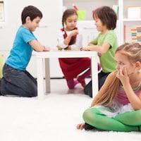 Une enfant en regarde d'autres en train de jouer.