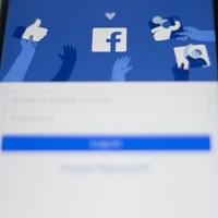 Un téléphone intelligent, déposé sur une table, montre l'écran d'accueil de Facebook.