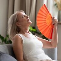 Une femme utilise un éventail pour se rafraîchir.