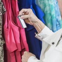 Une femme vérifie l'étiquette d'une pièce de vêtement dans un magasin.