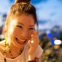 Une femme d'origine asiatique pleure tellement elle rit de bon cœur.