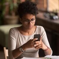 Une adolescente doute d'un contenu qu'elle consulte sur son téléphone intelligent.