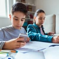 Deux adolescents font leurs devoirs à l'aide d'un ordinateur et d'un téléphone cellulaire.