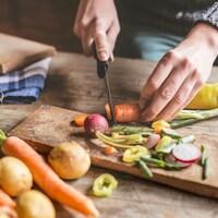 Une personne coupe des légumes sur une planche de bois.