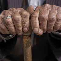 Les mains d'un homme âgé appuyées sur une canne.