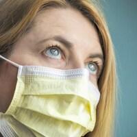 Une femme met son masque pour se protéger de la COVID-19.