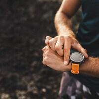 Une personne consulte sa montre sportive pendant une activité physique.