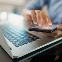 Une personne utilise un téléphone devant un clavier d'ordinateur portable.
