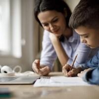 Une mère aide son enfant à faire ses devoirs.