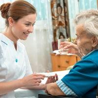 Une femme prodigue des soins à une patiente.