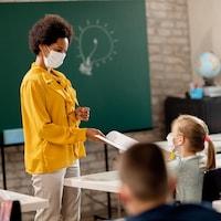 Une professeure regarde une de ses élèves dans sa classe.