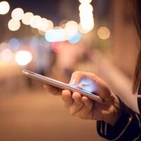 Une femme se sert de son téléphone intelligent dans la rue, le soir.