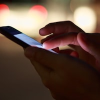 Gros plan sur les mains d'une personne manipulant un téléphone intelligent.
