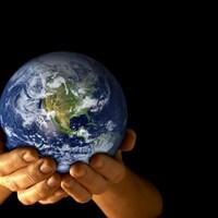 Une personne tient une réplique de la planète Terre dans ses mains.