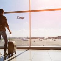 Un homme attend son vol dans un aéroport.