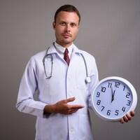 Dans un studio au mur gris, un homme médecin tient une horloge dans sa main gauche. Il la pointe de sa main droite.