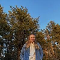 Une adolescente souriante debout devant des arbres.