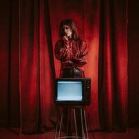 Mélissa Ouimet est debout derrière une vieille télévision placée sur un tabouret ; un rideau de scène en arrière plan