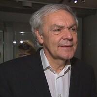 Le muséologue Michel Côté se trouve dans une pièce contenant une oeuvre d'art.