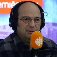 Michel Rivard derrière un micro dans un studio radio de Radio-Canada