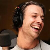Mickaël Gouin riant dans un studio de radio.