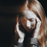 Image floutée d'une femme se tenant la tête et grimaçant de douleur.