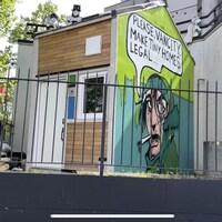Une mini-maison avec une murale dessinée sur un des murs.