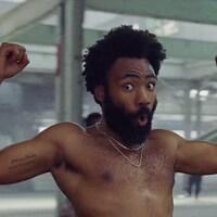 Le rappeur Childish Gambino, torse nu, lève les poings dans une scène du vidéoclip de la chanson <i>This Is America</i>.