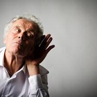 Un homme âgé met une main contre son oreille peut mieux entendre.