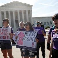 Quelques femmes vêtues de violet manifestent leur position en faveur de l'avortement en brandissant des pancartes sur lesquelles on peut lire « Démasquez les faux centres de santé des femmes » ou « Mon corps mon choix ».