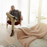 Un homme assis dans une belle pièce illuminée a une main au visage.