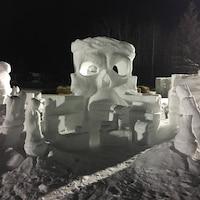 Des sculptures de neige dans un paysage hivernal nocturne.