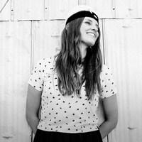 La chanteuse Émilie Clepper se tient tout sourire devant le mur en tôle d'un bâtiment.
