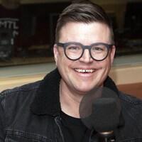 Un homme avec des lunettes regarde la caméra en souriant.