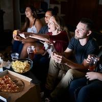 Des jeunes regardent la soirée électorale en prenant un verre.