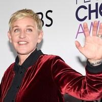 Ellen DeGeneres lève la main à quelqu'un.