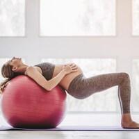 Une femme enceinte fait des exercices avec un ballon thérapeutique.
