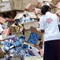 Une femme vue de dos observe un empilement de boîtes de médicaments.