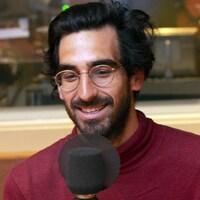 Un homme barbu sourit devant un micro.
