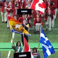 L'équipe canadienne aux derniers Jeux de la Francophonie, en 2016 à Abidjan, avec le drapeau du Nouveau-Brunswick.